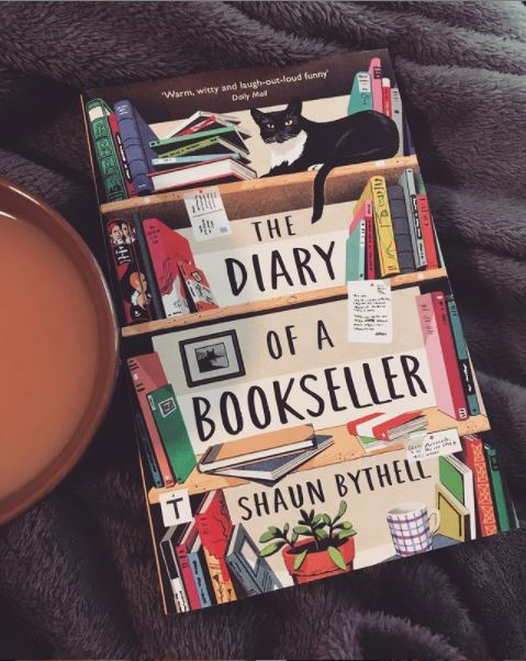 Buch liegt auf einer grauen Decke, links daneben sieht man eine Teetasse. Auf dem Cover des Buches ist ein buntes Bücherregal abgebildet, auf einem Regalbrett liegt eine schwarze Katze. In der Mitte sind die Regelareihe freien, dort steht der englische Titel des Buches: The Diary of a Bookseller