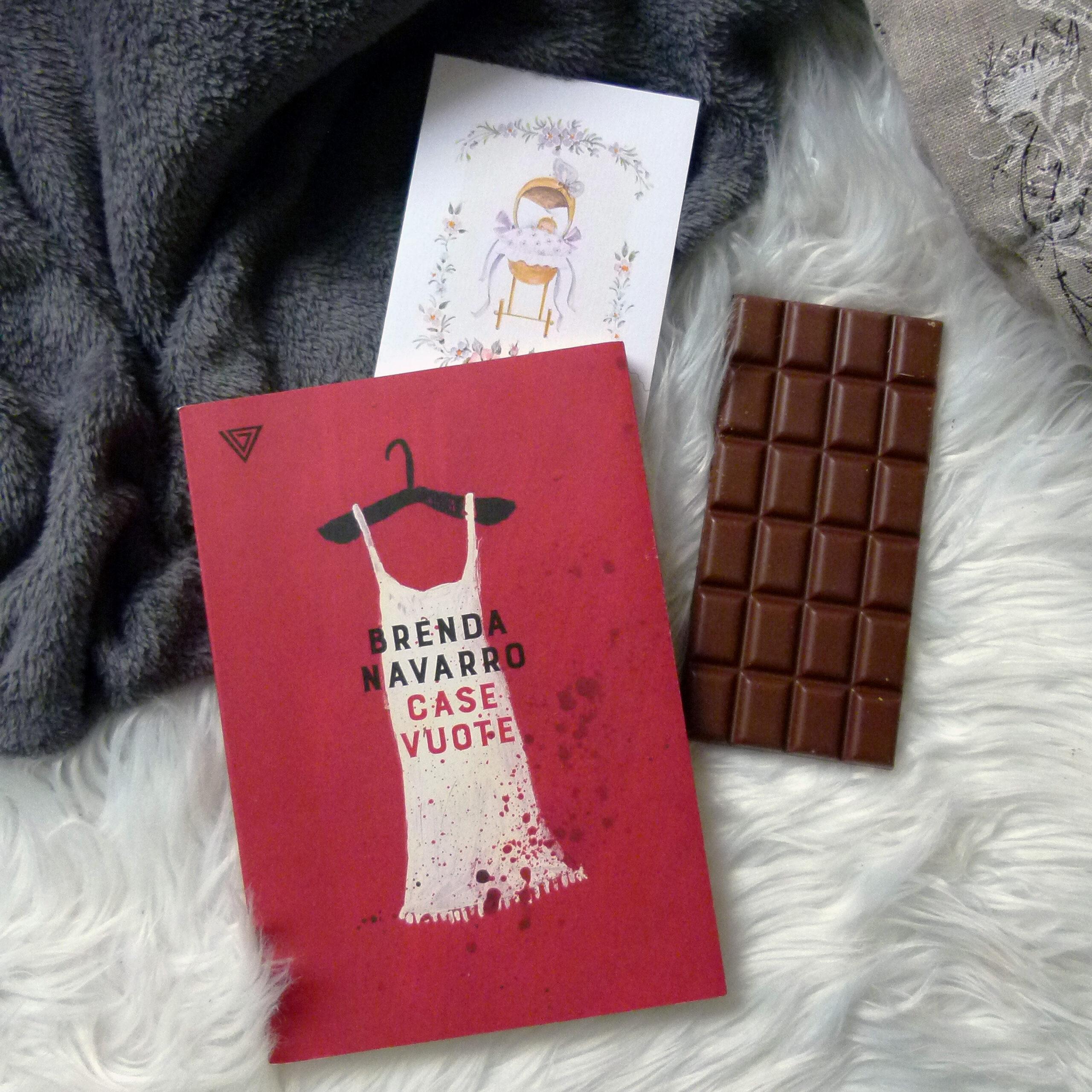 Das rote Buch liegt auf einem flauschigen weißen Hintergrund und einer grauen Decke. Oben rechts lugt noch ein Teil eines grauen Kissens mit dekorativer, schwarz-weißer Schrift ins Bild. Das Cover ist rot mit einem weißen, Kleid auf einem schwarzen Bügel. Darauf steht in schwarzer Schrift der Name der Autorin und in rot darunter der italienische Titel