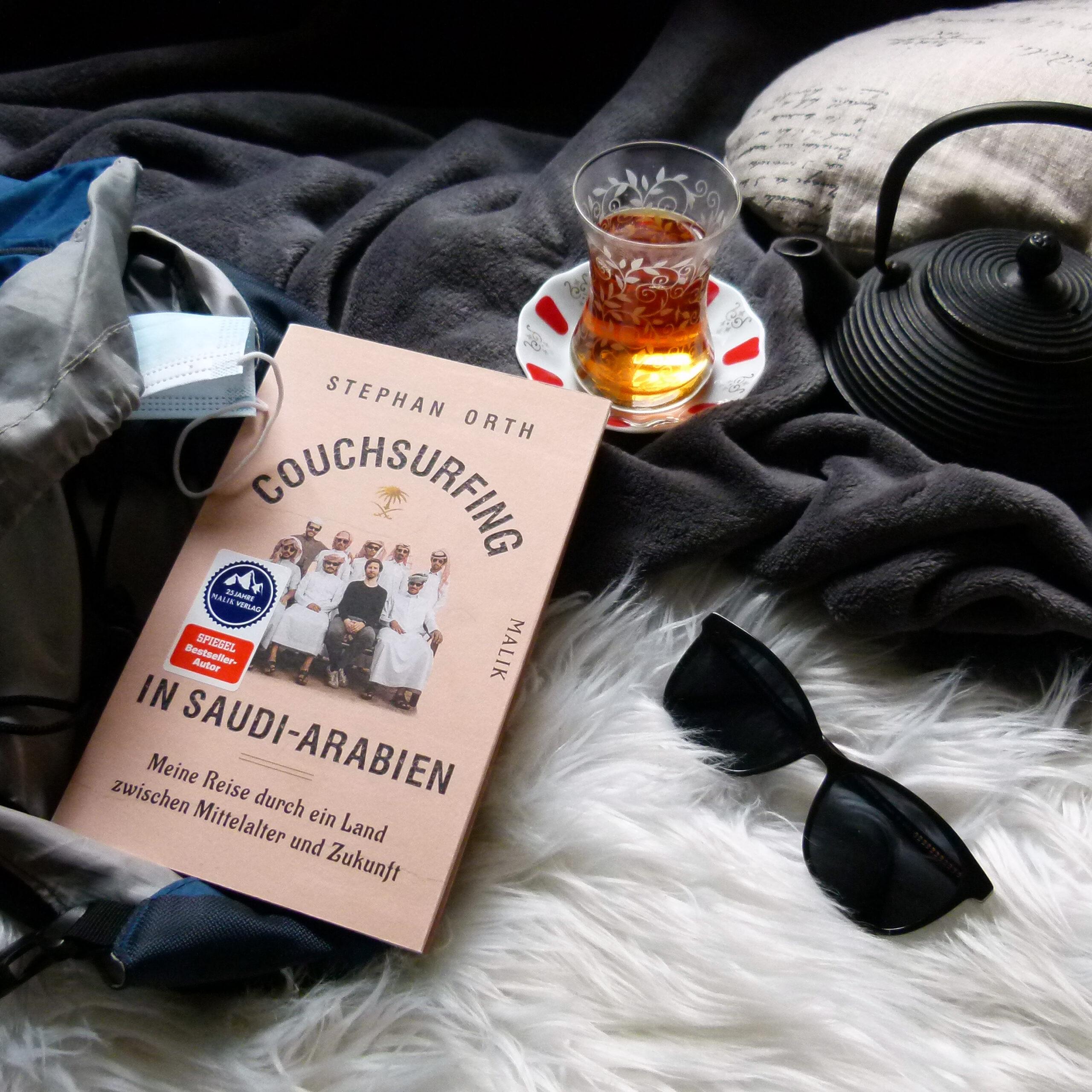 Das wüstenfarbene Buch liegt auf einem weißen, flauschigen Untergrund. In der oberen Hälfte des Bildes liegt eine dunkelgraue, ebenfalls flauschige Decke. Darauf (in der rechten Ecke) ein graues Kissen, schräg darunter eine Terracotta-Kanne und links daneben ein Teeglas auf einem rot-weißen Unterteller. Links im Bild ist ein blau-grauer Reiserucksack sichtbar, aus dem ein Mundnasenschutz herausragt. Neben dem Buch liegt eine Sonnenbrille mit dunklem Gestell.