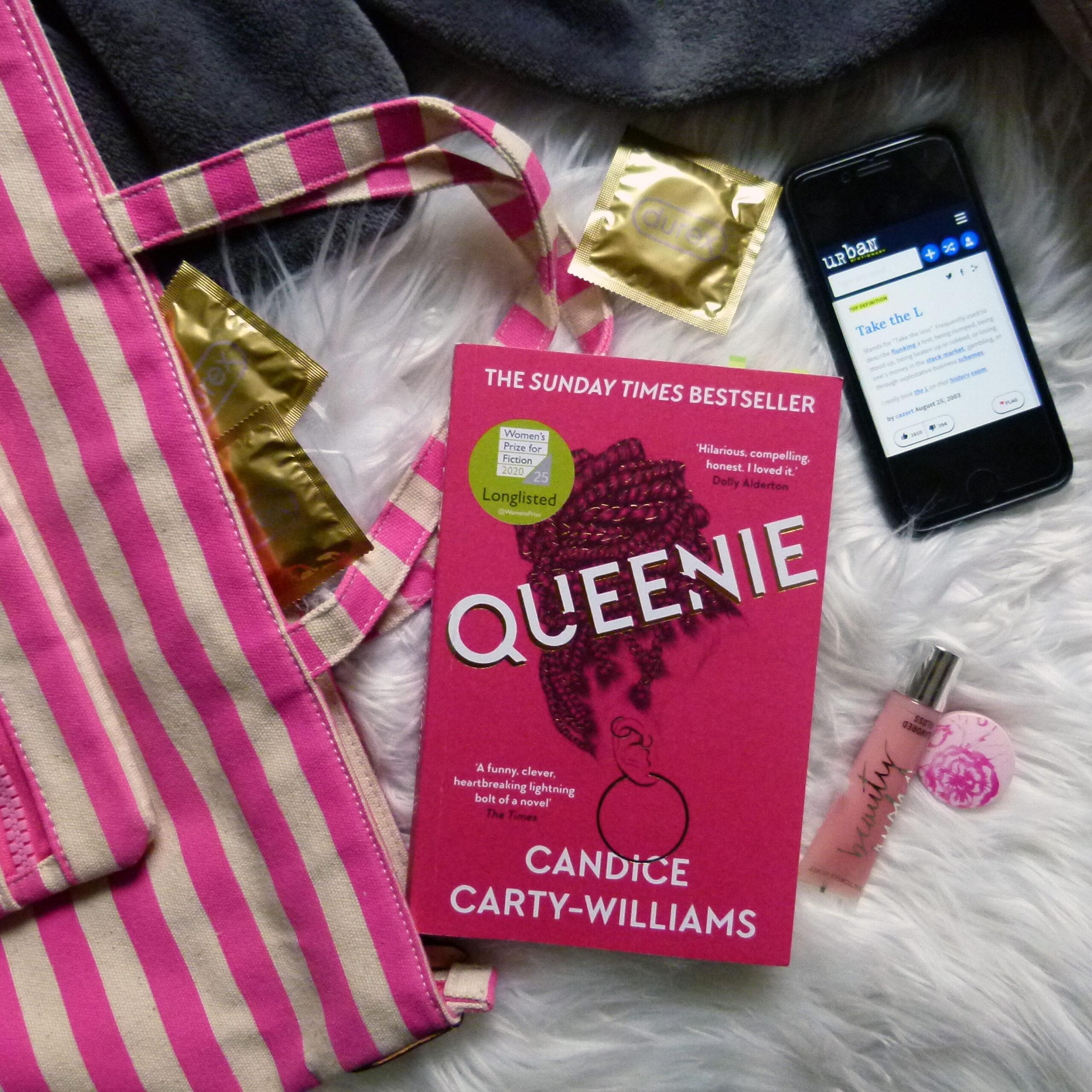 Das mittig im Bild gelegene Buch (pinkes Cover mit einem stilisiertem Frauenkopf mit Braids, Ohrringen. Titel