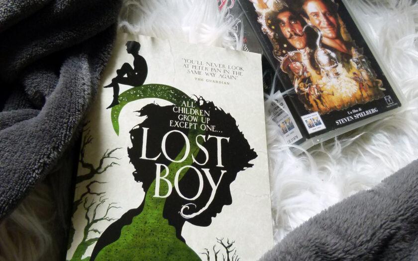"""Auf einem weißen Teppich und einer grauen Decke liegt die englische Ausgabe des Buches im Vordergrund. Im Hintergrund sieht man das Cover einer Videokassette des Films """"Captain Hook""""."""