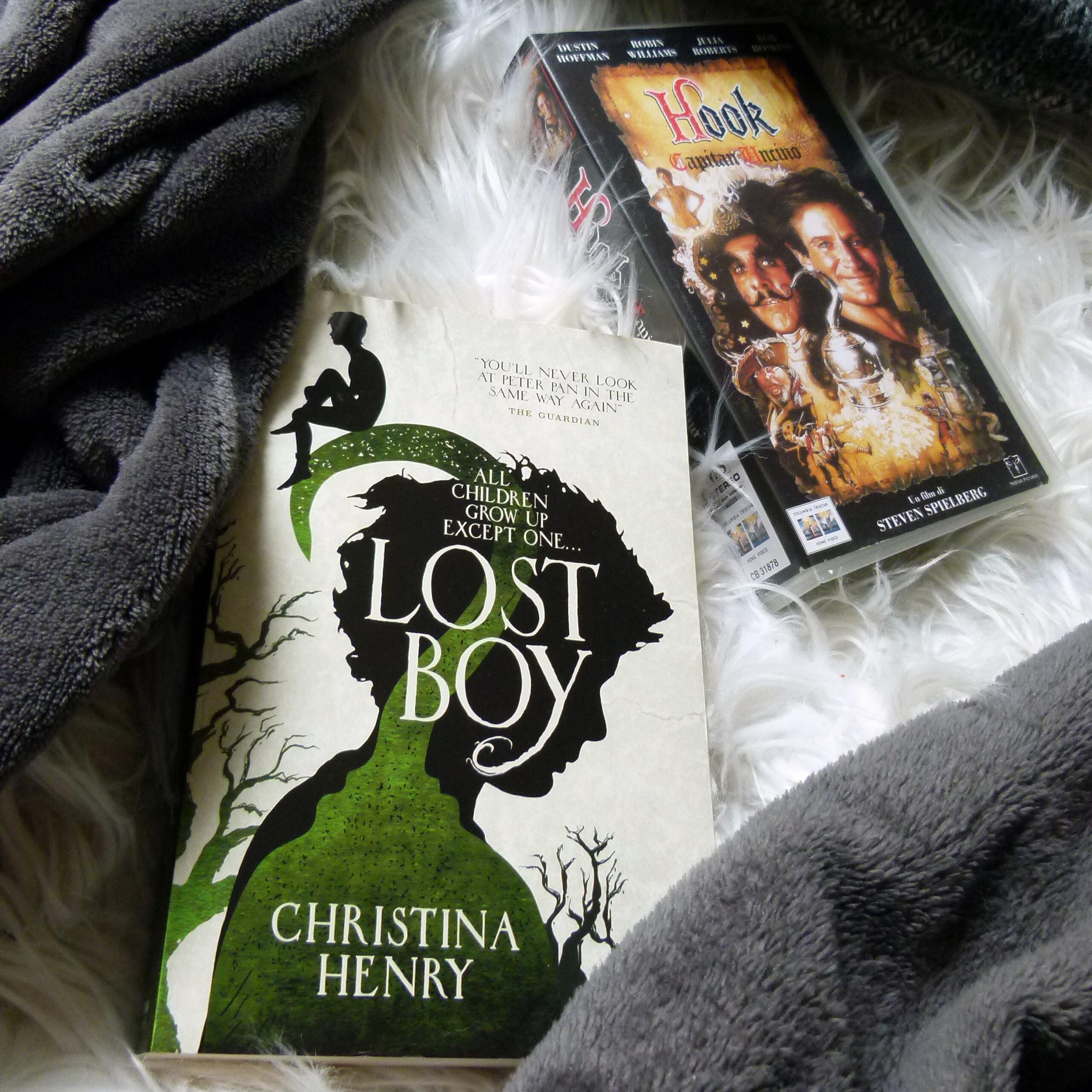 Auf einem weißen Teppich und einer grauen Decke liegt die englische Ausgabe des Buches im Vordergrund. Im Hintergrund sieht man das Cover einer Videokassette des Films
