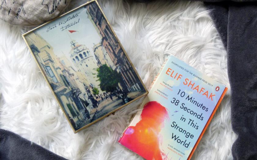Das Buch liegt mittig im Bild. Links davon liegt eine Schatulle. Auf der Schatulle ist eine Straße Istanbuls abgebildet, die zum Galata Turm führt