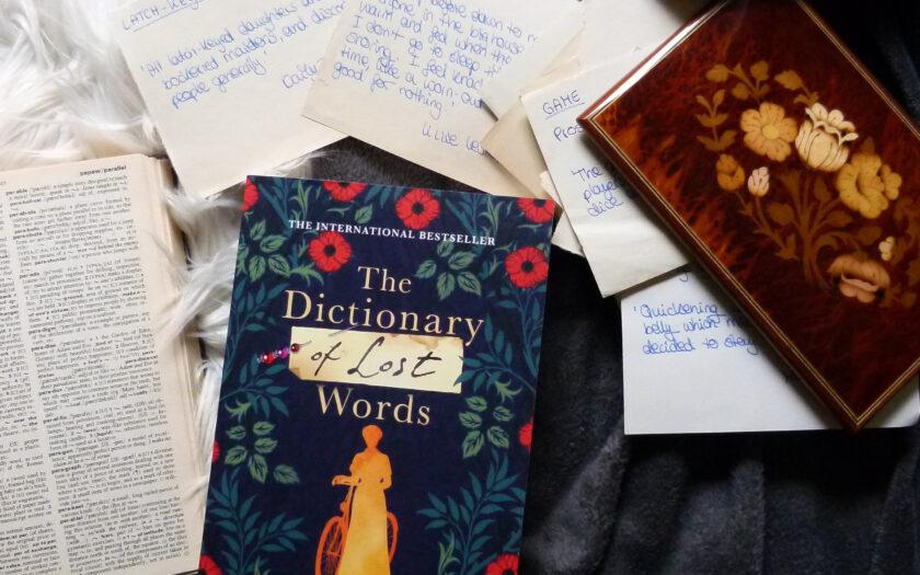 Das Buch liegt zentriert auf einem grau-weißen Hintergrund. Links liegt ein aufgeschlagenes Wörterbuch. Rechts liegt eine Schatulle mit floralem Muster aus der Belegzettel herauslugen. Im oberen bereich liegen ebenfalls Papierzettel.